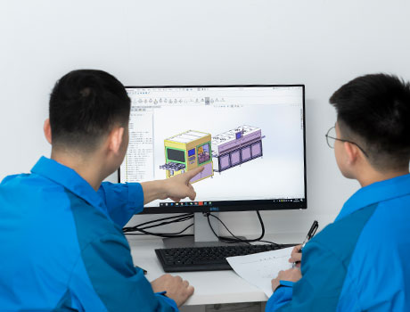 2 research personnel discussing in front of a computer showing engineering drawing of a machine layout